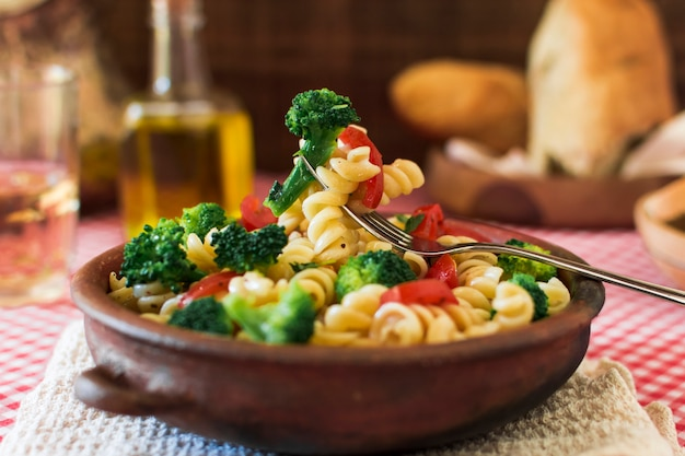 Close-up of delicious fusilli pasta salad with fork