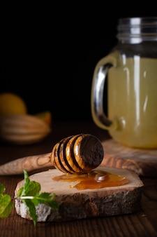 Close-up delicious honey stick and lemonade jar
