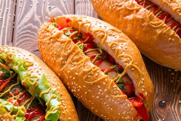 Закройте вверх по вкусным хот-догам на деревянном столе