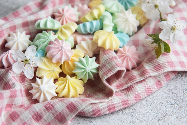 Close-up delicious meringue cookies pastel colors. french pastries, sweet crunchy swirls candy