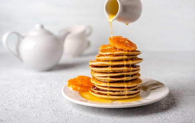 밝은 배경에서 아침 식사를 위해 꿀 또는 메이플 시럽을 곁들인 근접 맛있는 팬케이크. 시럽을 팬케이크에 붓습니다.