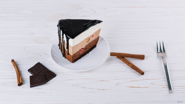 Close-up of delicious pastry; cinnamon; chocolate bar; fork
