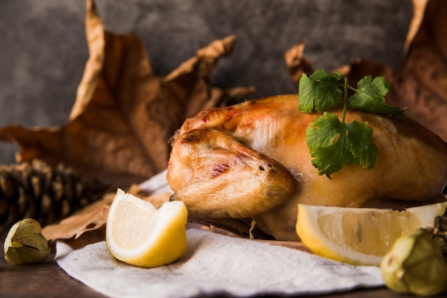 Close-up of a delicious roasted chicken with lemon slice on table cloth