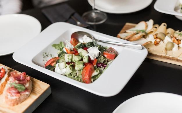 Крупным планом вкусный салат и закуски на столе