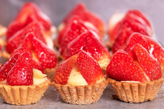 Close up of delicious tartlets with fresh strawberries and vanilla cream.