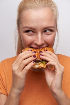 Close-up of delighted young pretty long haired blonde woman with natural makeup enjoying her burger while having fast dinner, smiling cheerfully and looking aside, isolated over white background