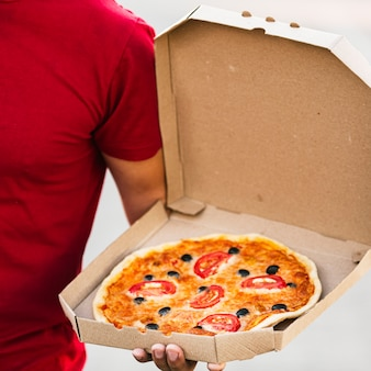 Close-up delivery guy holding pizza box