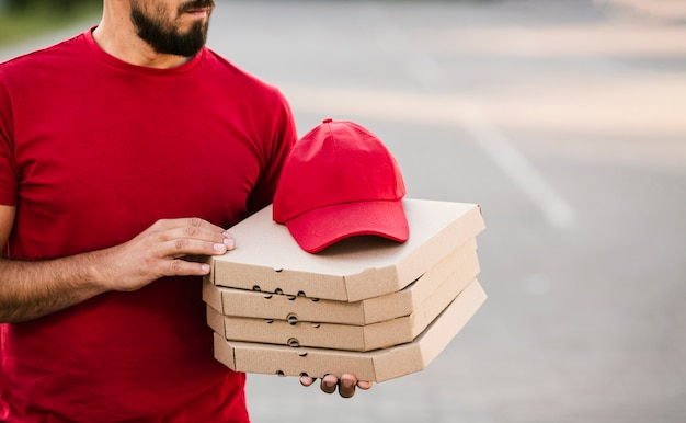 Close-up delivery guy holding pizza boxes