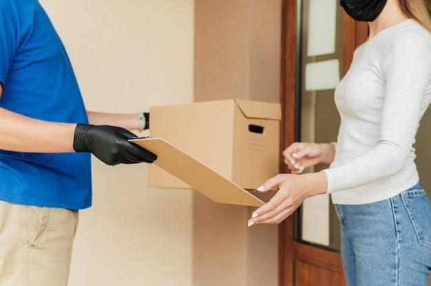 Крупный план доставки человек, дающий коробку