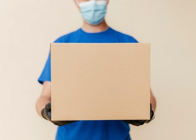Крупный план доставки человек, держащий коробку