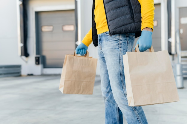 Close-up delivery man holding paper bags