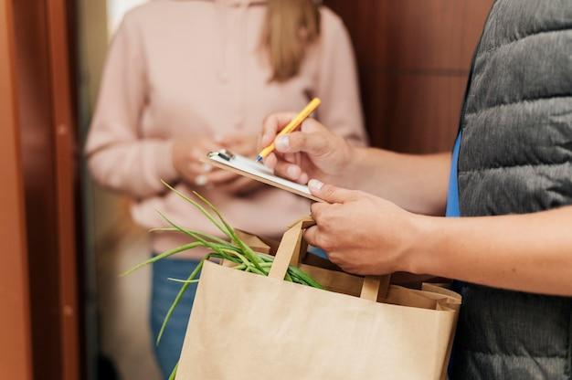 Крупным планом доставщик подписывает бумагу