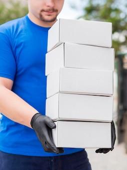Uomo di consegna del primo piano che indossa guanti neri