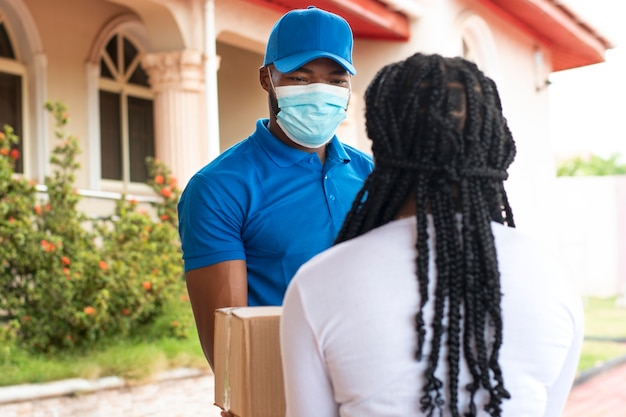Close up on delivery person giving parcel to client