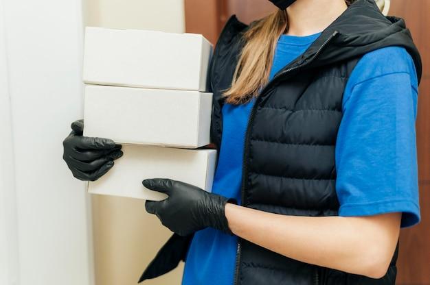 Женщина доставки крупным планом, держащая коробки