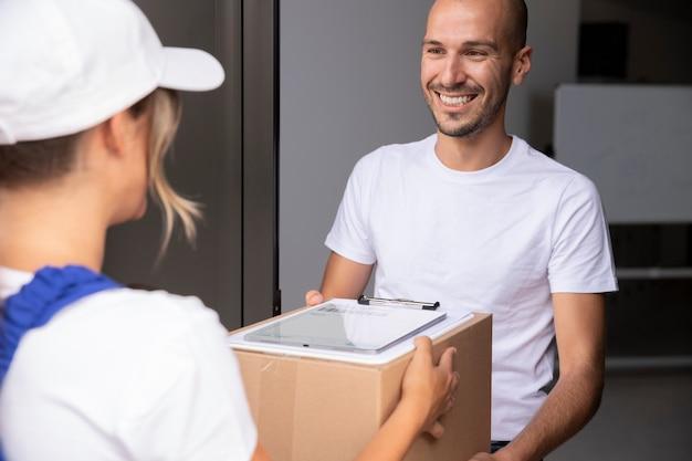 Крупным планом женщина доставки, держащая пакет
