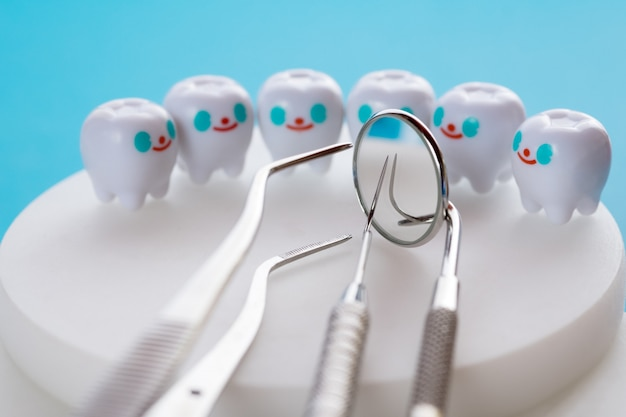 Close up.dental tools and smile teeth model on blue background.
