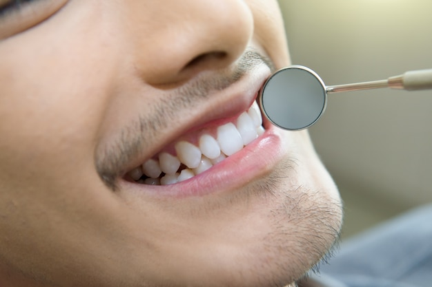 Close up dentist checking patient teeth with metal reflector