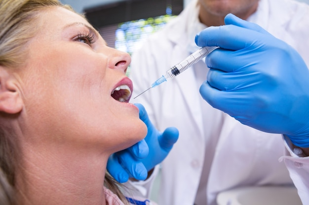Close up of dentist holding syringe by patient