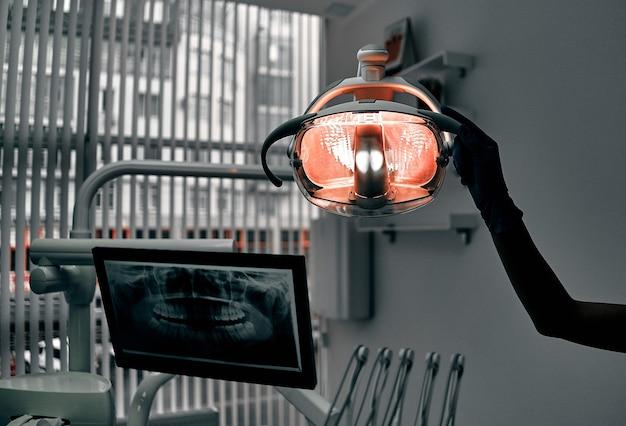クローズアップ歯科医ランプ。クリニックでの歯科治療。操作、歯の交換。医学、健康、口腔病学の概念。歯科医が検査を行い、結論を出すオフィス。