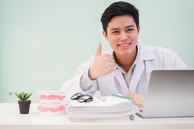 Close up dentist man show thumb up hand for good health at office desk