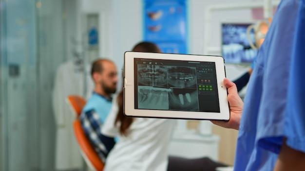 医師が歯科医院の口腔病学の椅子に座って歯の問題を調べているバックグラウンドで患者と一緒に働いている間、デジタルラジオグラフィーでタブレットを持っている歯科医の看護師を閉じてください。