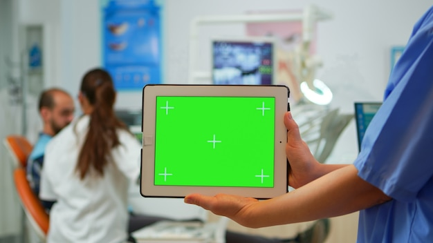 Close up dentist nurse holding tablet with greenscreen display standing in stomatologic clinic, while doctor is working with patient in background. using monitor with chroma key izolated pc key mockup