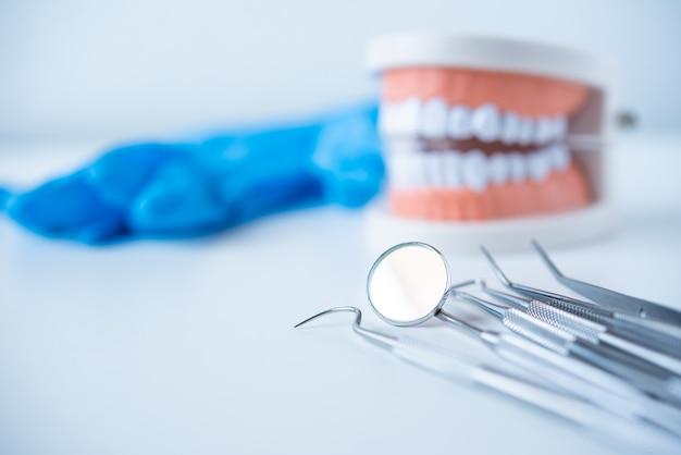 Крупным планом инструменты стоматолога для ухода за зубами на белом фоне вид сверху