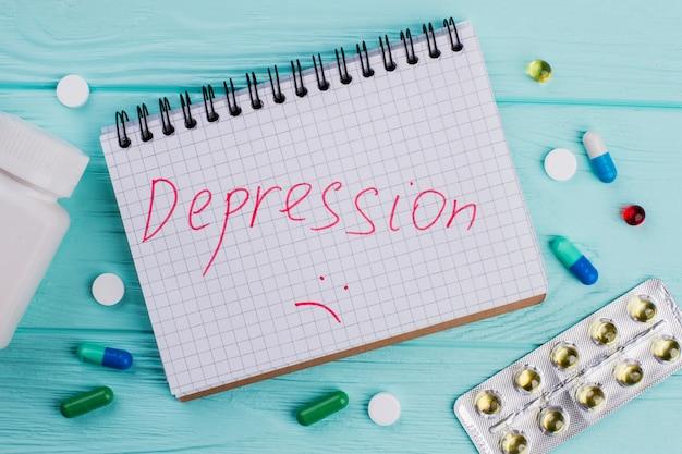 클로즈업 '우울증'은 다른 알약으로 둘러싸여 있습니다. 파란색 질감된 배경입니다.