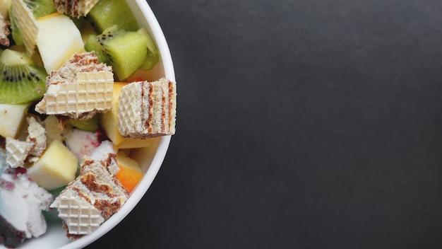 신선한 과일과 아이스크림으로 사막을 닫습니다. 검은 표면에 와플과 과일 얼음과 혼합 과일