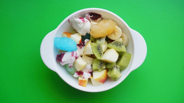 Close up desert with fresh fruit and ice cream. mixed fruit with with fruit ice on green surface