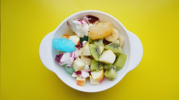 Close up desert with fresh fruit and ice cream. mixed fruit with with fruit ice on yellow surface