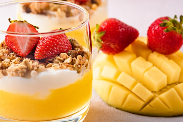 Close up dessert with ricotta cheese, mango, granola and strawberries on pink background. tropical dessert concept