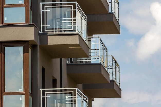 Close-up detail of apartment building wall with balconies and shiny windows on blue sky .