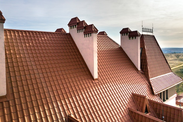 Close-up detail of building steep shingle roof and brick plastered chimneys on house top with metal tile roof. roofing, repair and renovation work.