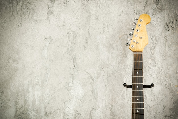 Close up detail of an electric lead guitar with old brick wall background.