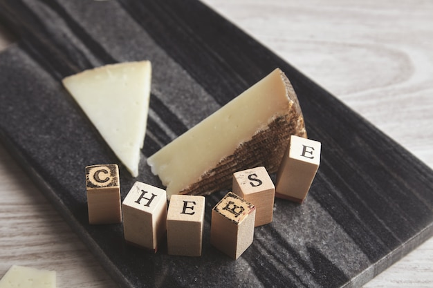 Close up detail focused wooden letter brick near unfocused goat cheese isolated on marble stone board on white wooden table