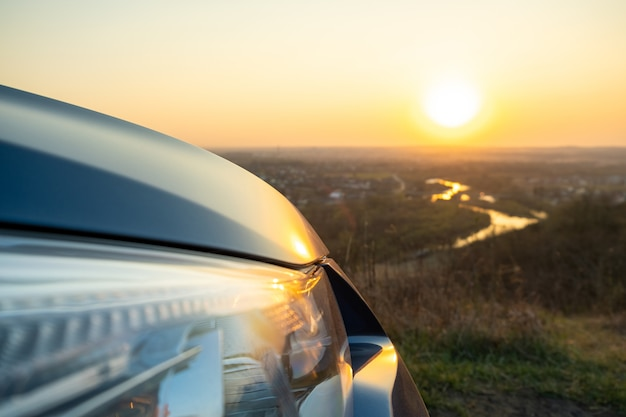 Close up detail of front headlight lamp of modern car at sunset.