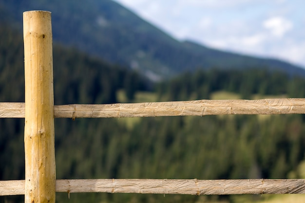 Close-up detail of low rough wooden fence on lit by bright summer sun