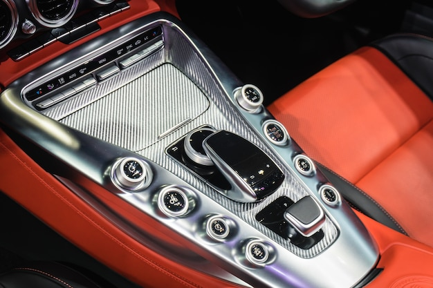 Close up of detail modern luxury car interior - steering wheel, shift lever and dashboard