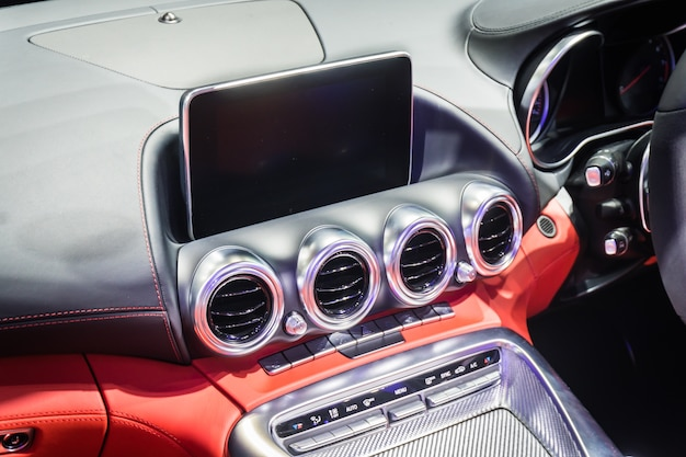 Close up of detail modern luxury car interior - steering wheel, shift lever
