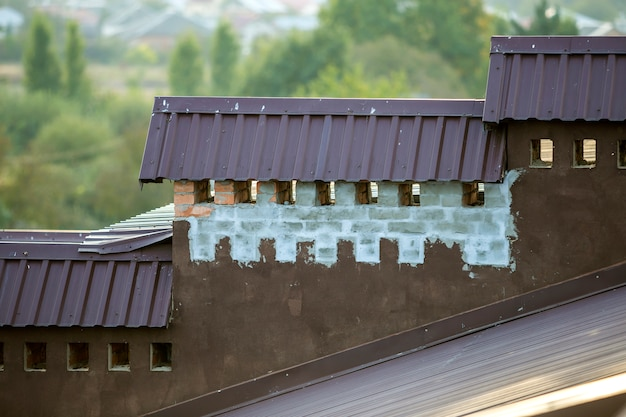 Close-up detail of new built brick plastered chimneys on house top with metal tile roof.