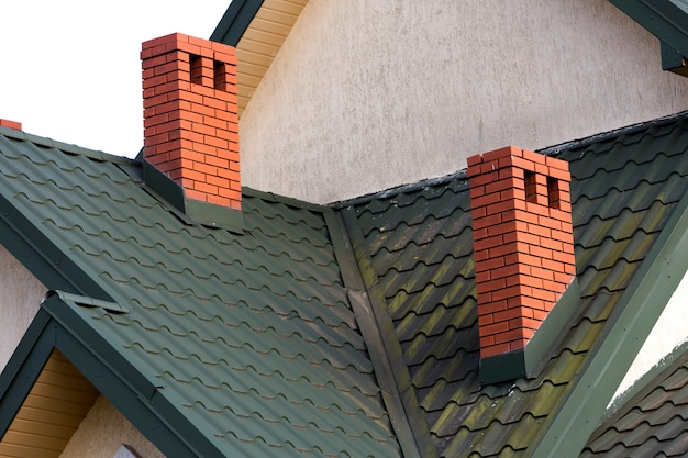 Close-up detail of new modern house top with shingled green roof