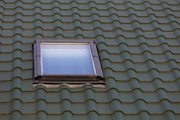 Close-up detail of new small attic plastic window installed in dark green shingled house roof background