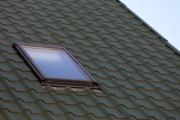 Close-up detail of new small attic plastic window installed in dark green shingled house roof
