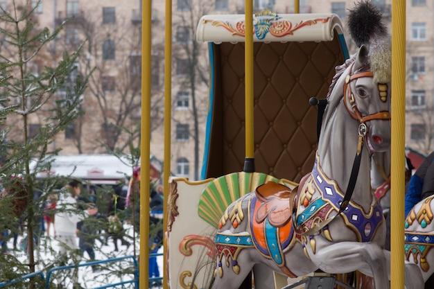都会の広場で冬のカーニバルで子供のためのメリーゴーランドやカーニバルで鮮やかに描かれたカラフルな馬の詳細をクローズアップ