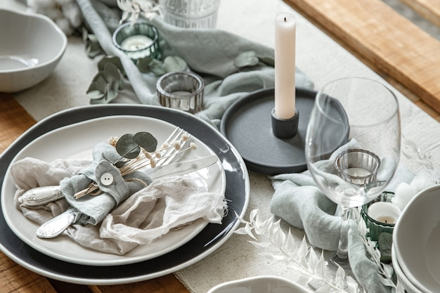 칼 붙이, 접시 및 촛대에 촛불의 집합으로 축제 테이블 설정의 세부를 닫습니다.
