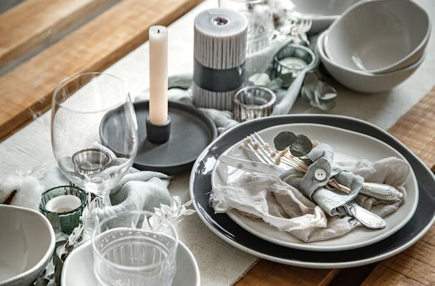 カトラリー、プレート、燭台のキャンドルのセットでお祝いのテーブルセッティングの詳細をクローズアップします。