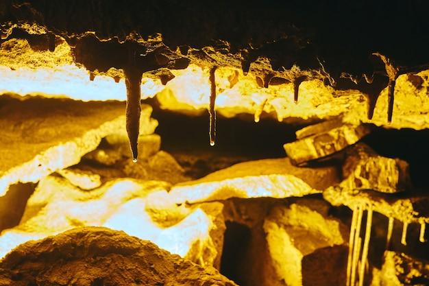 Крупным планом деталь сталактитов образования пещеры с водой на формировании подсказок
