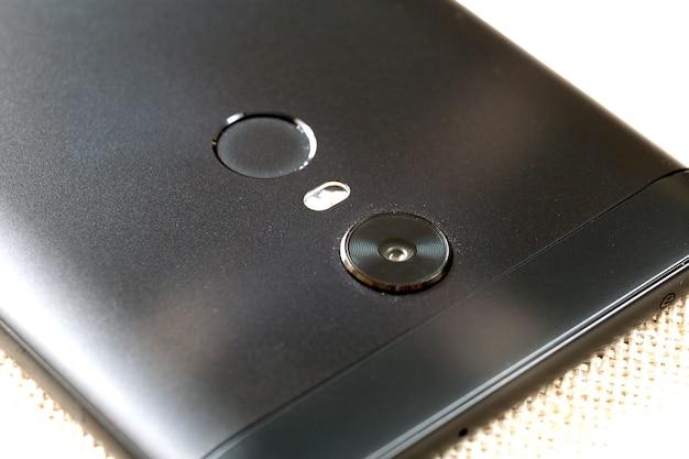 보안 엄지 지문 스캐닝 장치 및 카메라와 핸드폰의 근접 세부 사항. 현대 기술 보안 및 스마트 폰 디자인 컨셉입니다.